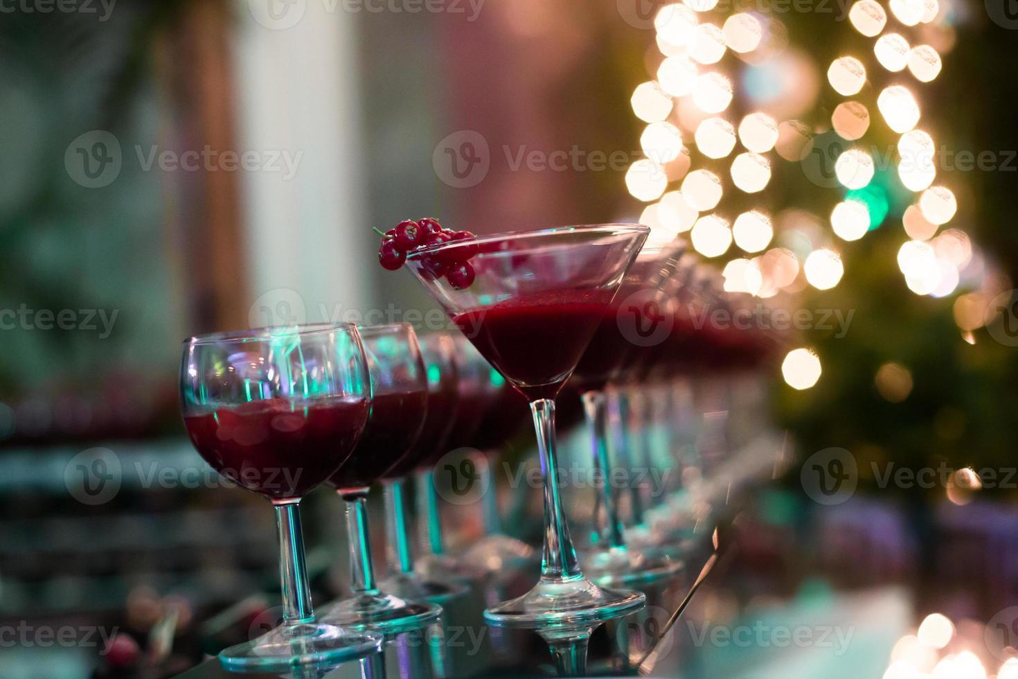 rad med olika färgade alkoholcocktails på en utomhusfest foto