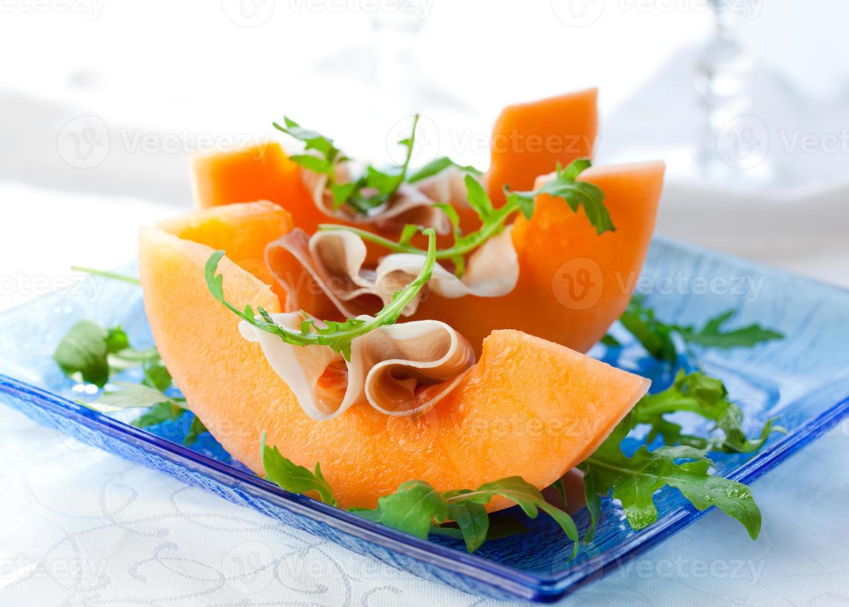 förrätt bestående av cantaloupe och prosciutto skivor foto