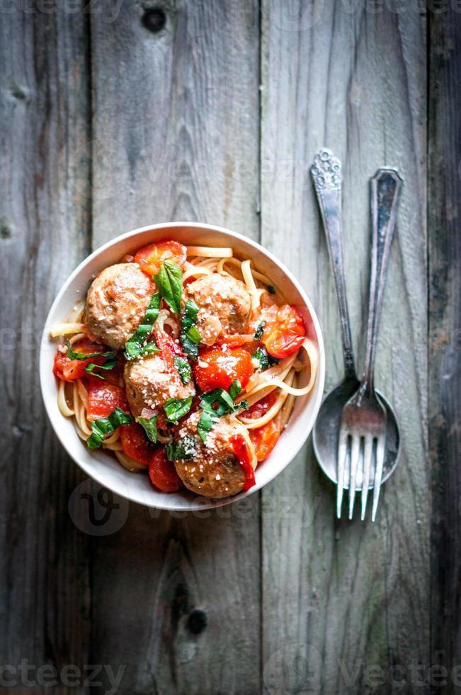 pasta med köttbullar på rustik bakgrund foto