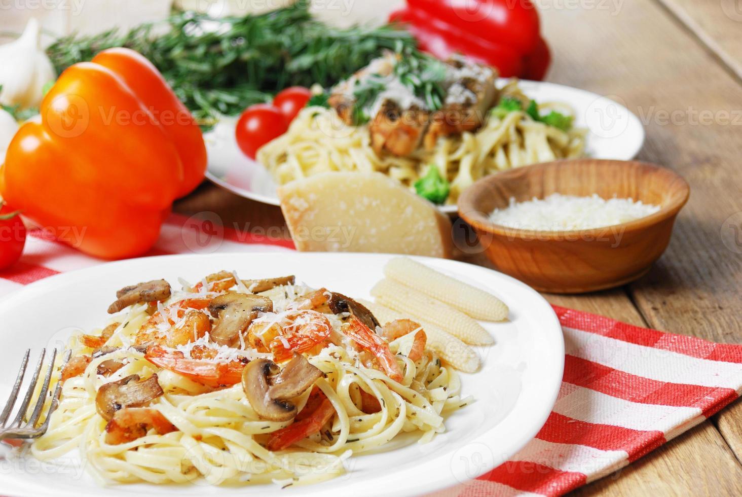 pasta med räkor och champinjoner på träbordet foto