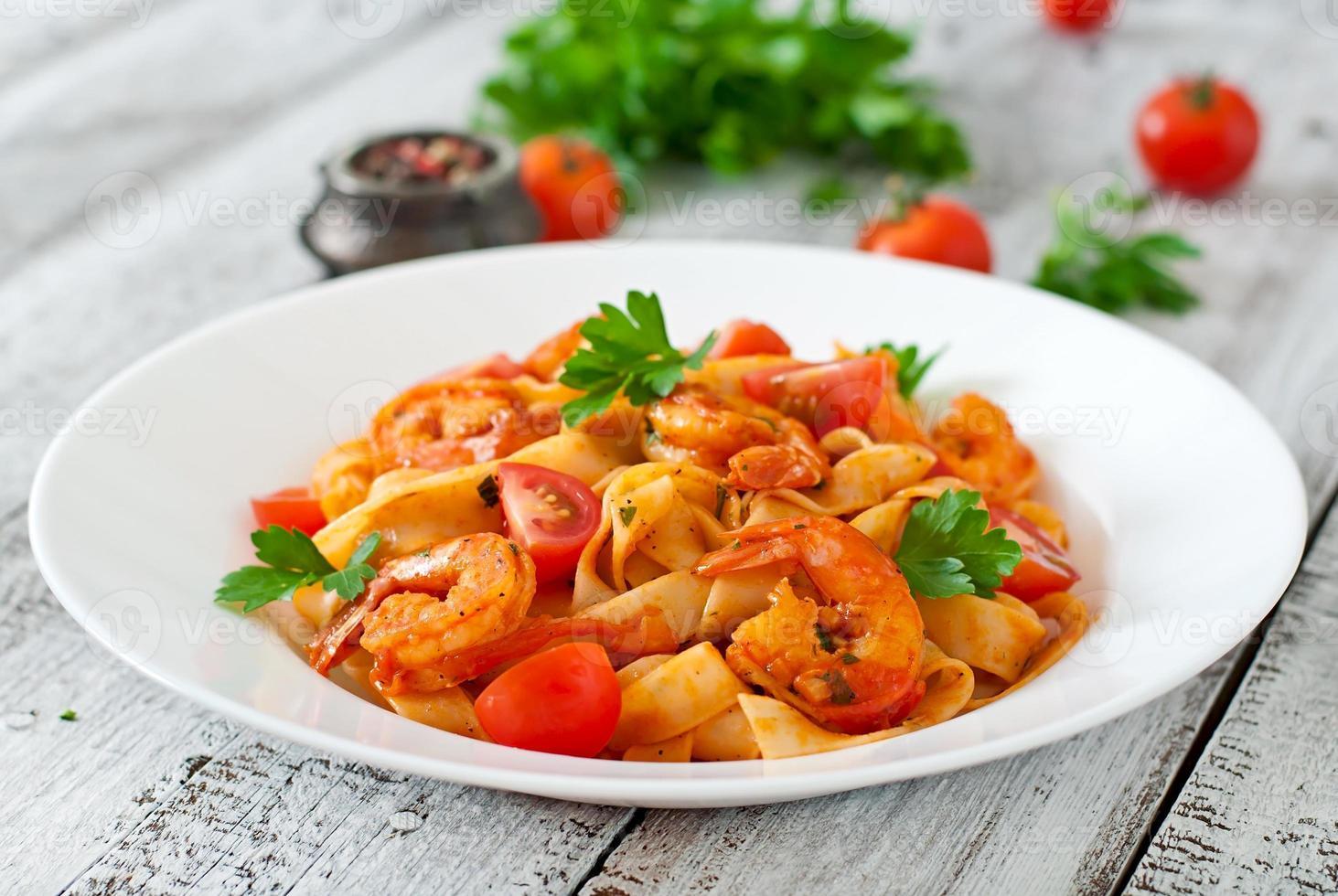 fettuccinapasta med räkor, tomater och örter foto