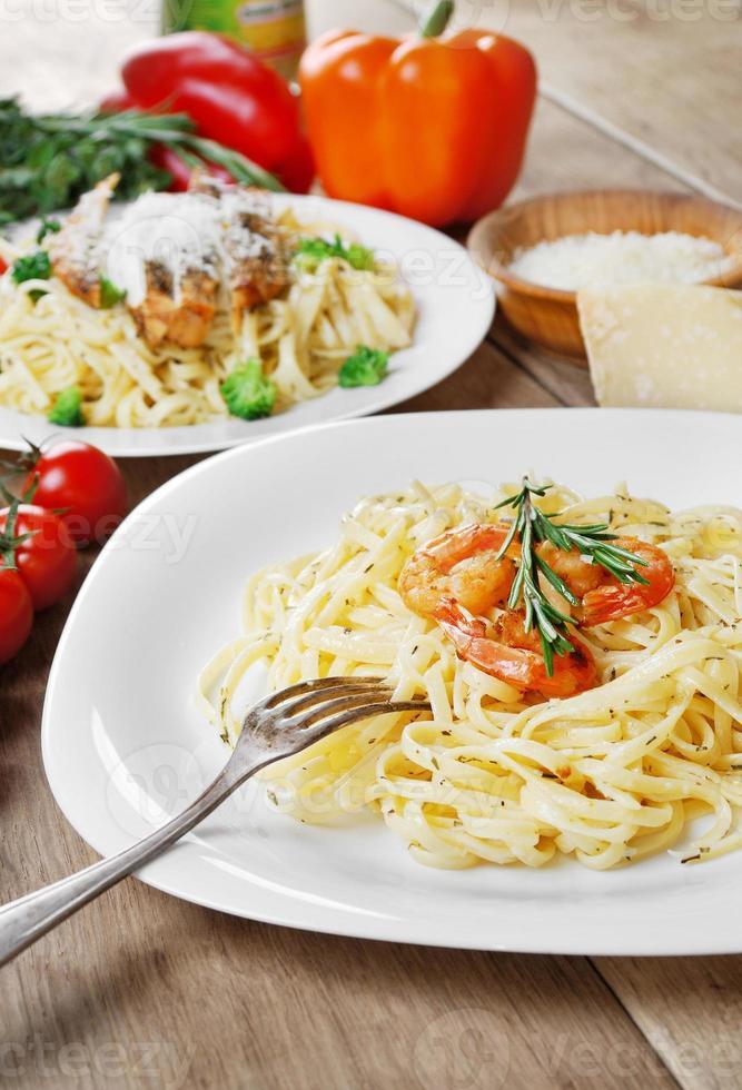 pasta med räkor och sås på träbordet foto
