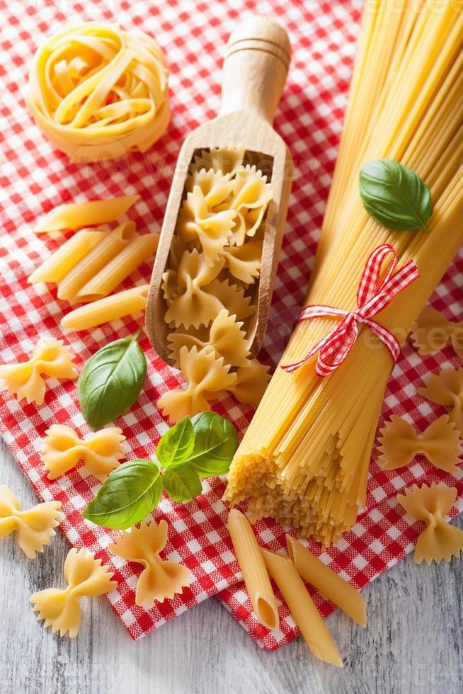 rå pasta farfalle spaghetti penne tagliatelle. italiensk mat foto