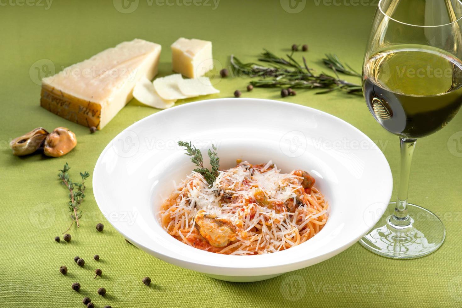 spaghetti med musslor, tomatsås och basilika foto