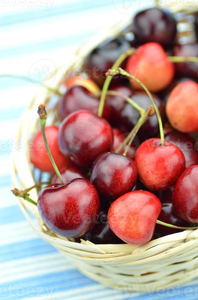 närbild av mogna färska och söta körsbär i rottingkorg foto