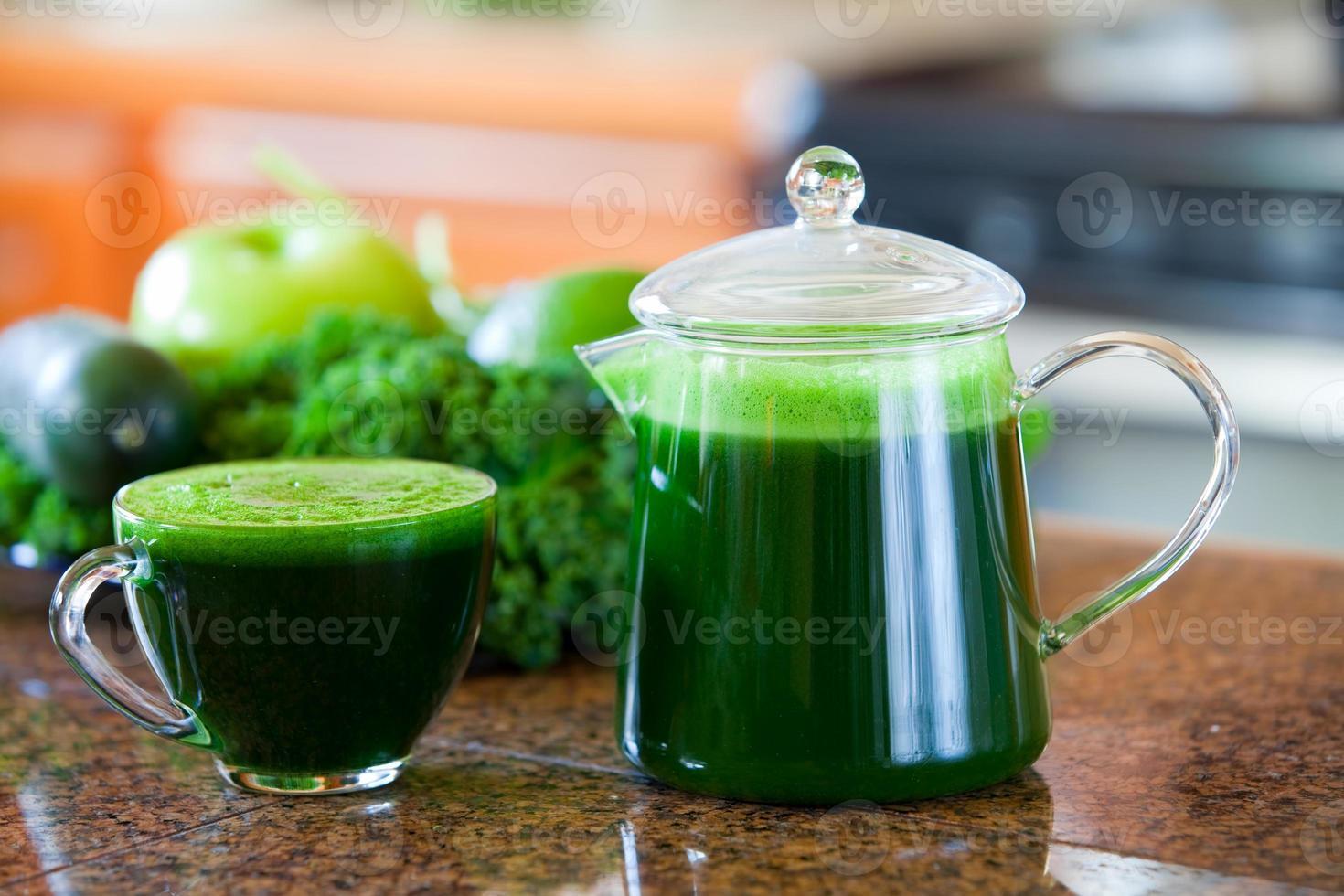 glas kopp grön grönsakssaft på köksbänken foto