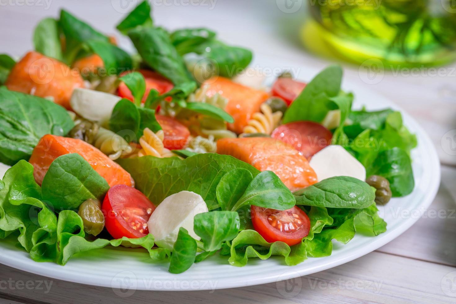 närbild av sallad med färska grönsaker och lax foto