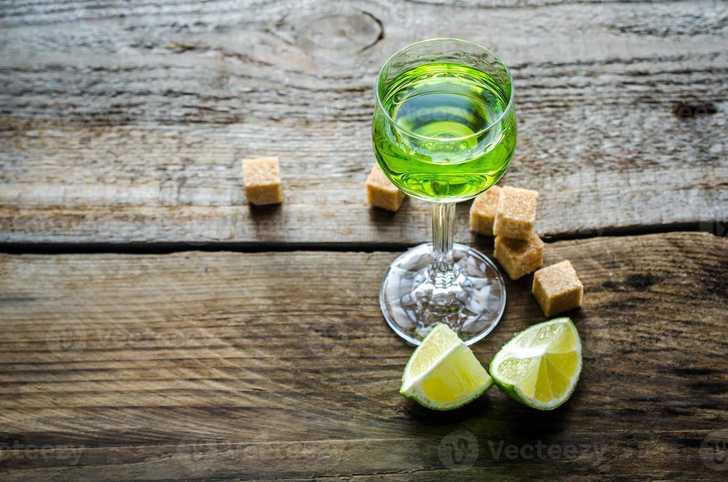 ett glas absint med kalk och sockerbitar foto