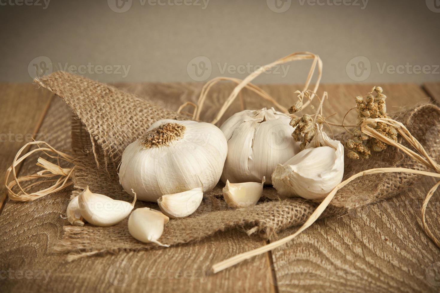 organisk vitlök hela och kryddnejlika på trä bakgrund foto
