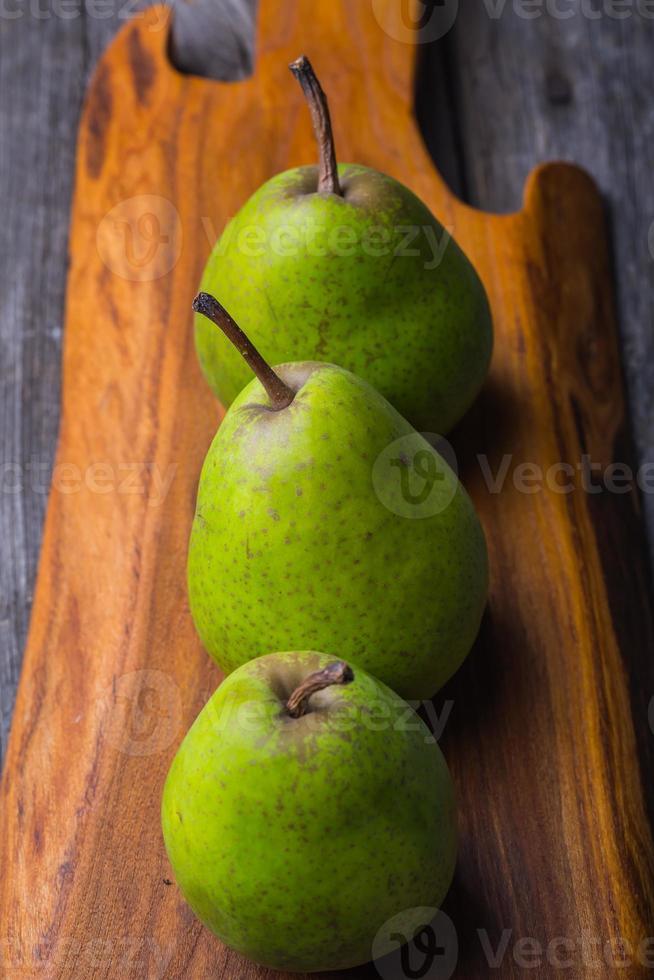 päron på träskärbräda och forntida träbord foto