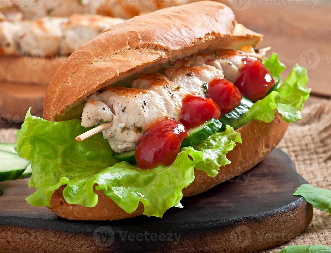 stor smörgås med kycklingkebab och sallad foto