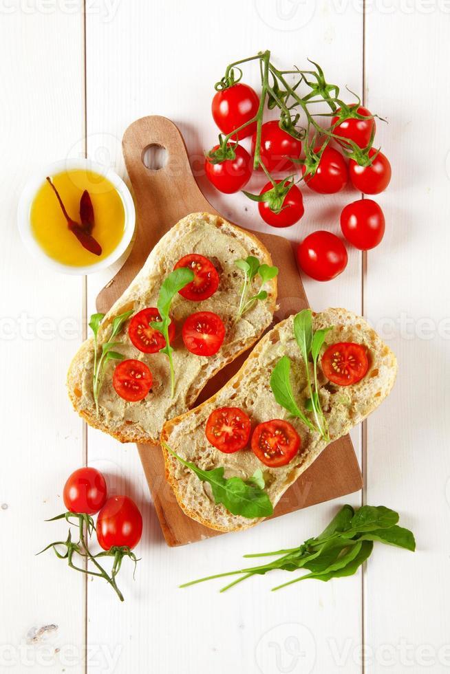 smörgås med körsbärstomater och grädde avokado och rucola foto