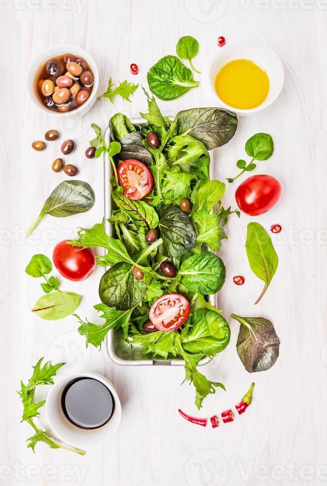 sallad med tomater, oliver, olja och vinäger på vitt trä foto