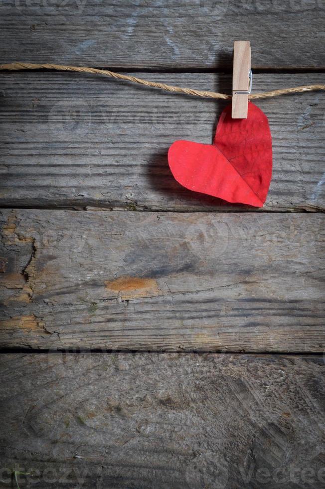 rött hjärta som hänger på klädstrecket. på gammal träbakgrund. foto