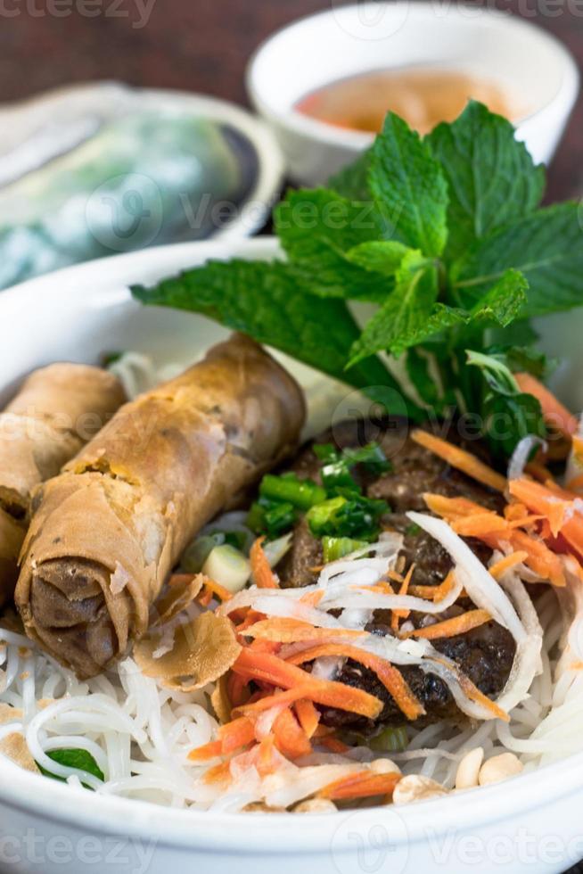 vietnamesisk bbq-fläsk med eggrolls på vermicelli foto