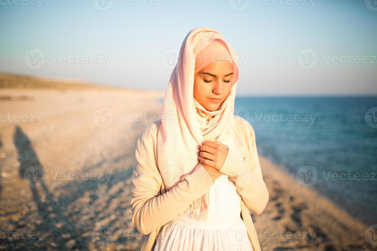 ödmjuk muslimsk kvinna som ber på stranden. spirituell religiös kvinna foto