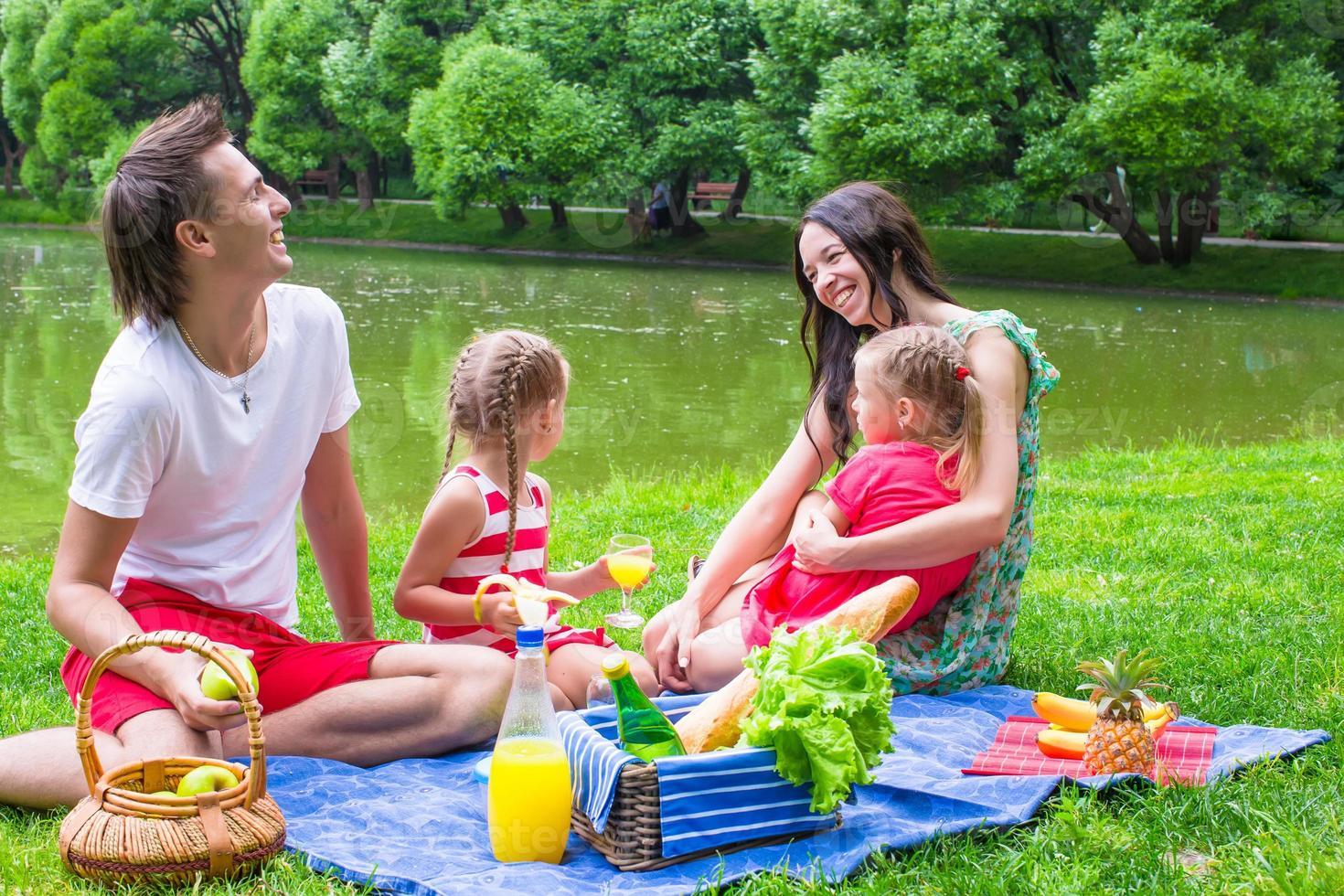 glad ung familj som picknick utomhus nära sjön foto