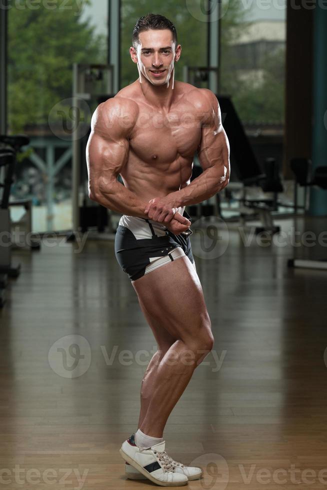 unga kroppsbyggare böja muskler foto