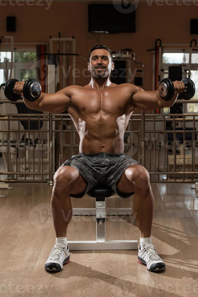 kroppsbyggare tränar axlar foto