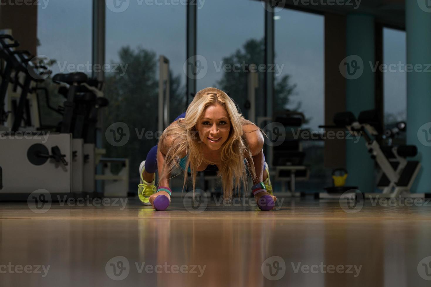 frisk medelålders kvinna som gör push up-övning foto