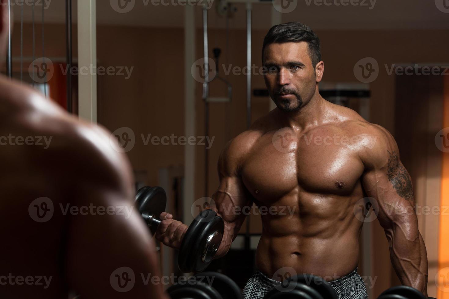 kroppsbyggare som gör träning med tung vikt för biceps foto