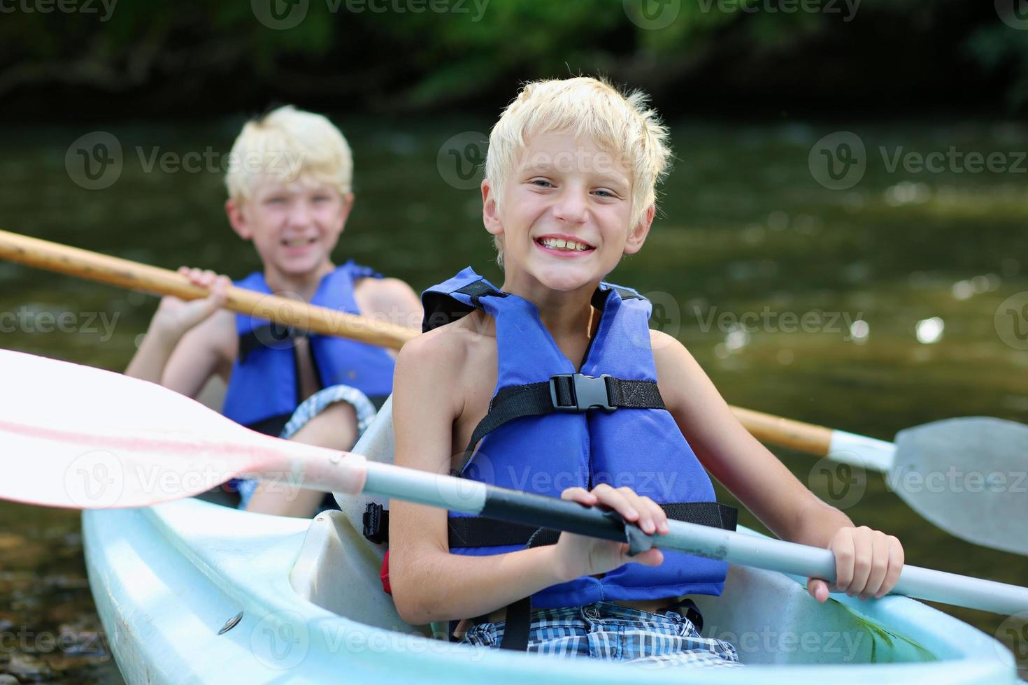 två glada pojkar som njuter av kajak på floden foto