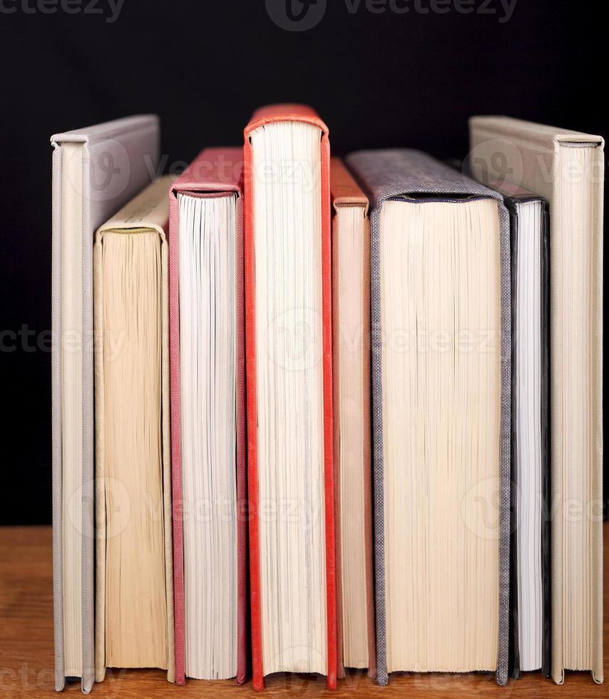 rad böcker på bokhylla. svart bakgrund. foto