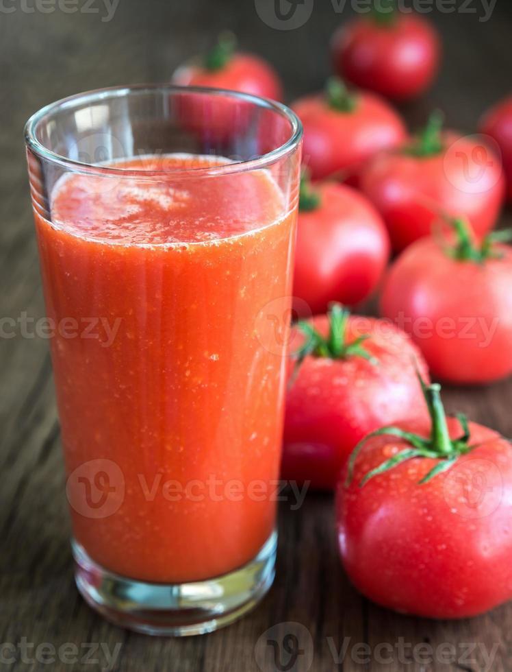 tomatsaft med färska tomater foto