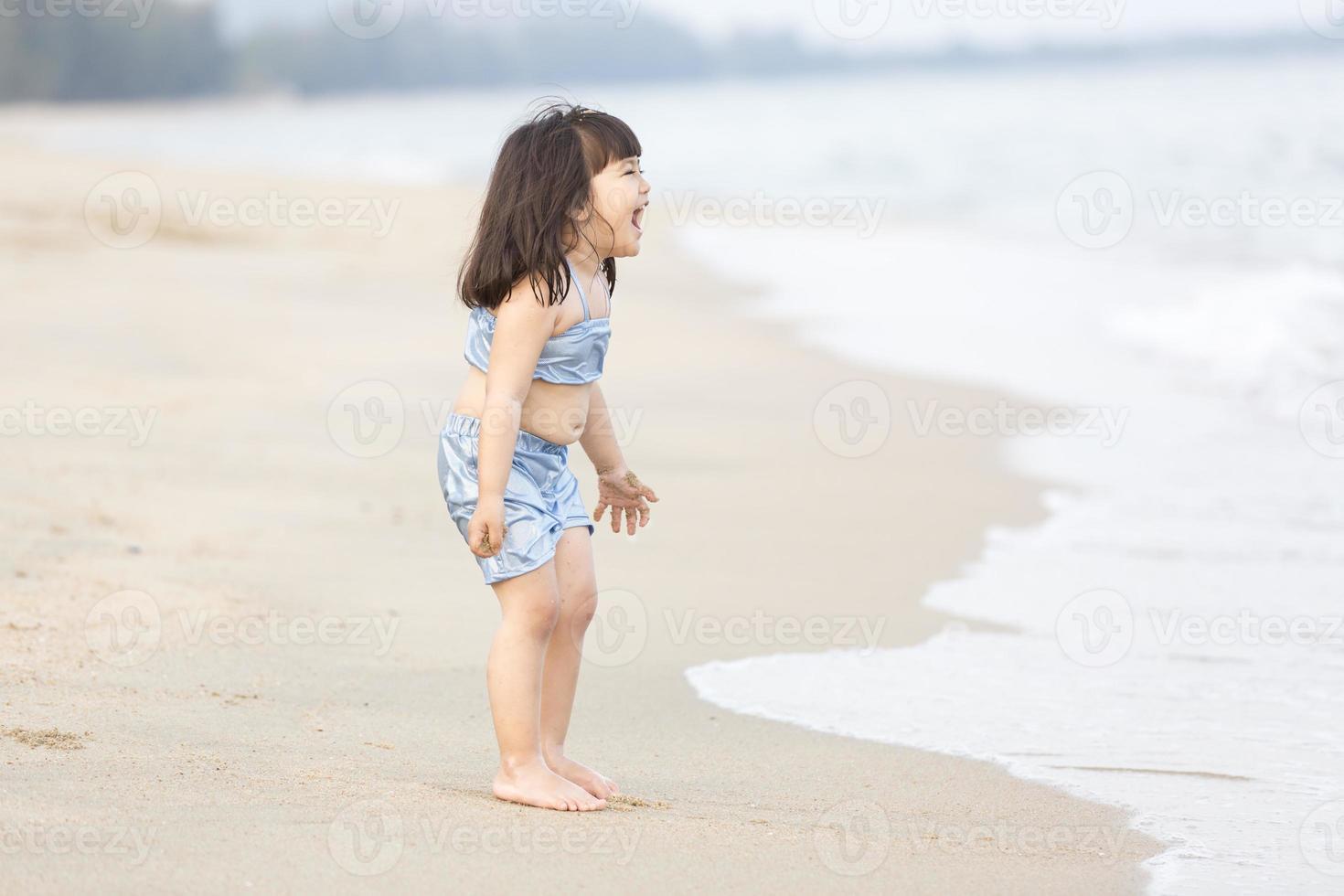 söt asiatisk tjej på stranden foto