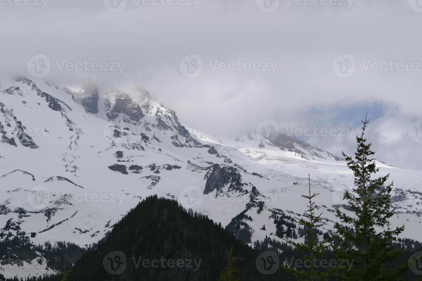 moln lyfta över snötäckta berg foto