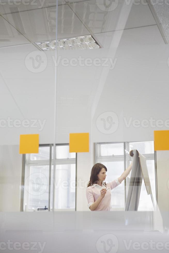 affärskvinna tittar på blädderblock i office foto