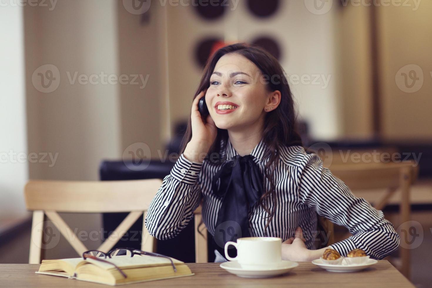 tjej som pratar i telefon på ett kafé foto