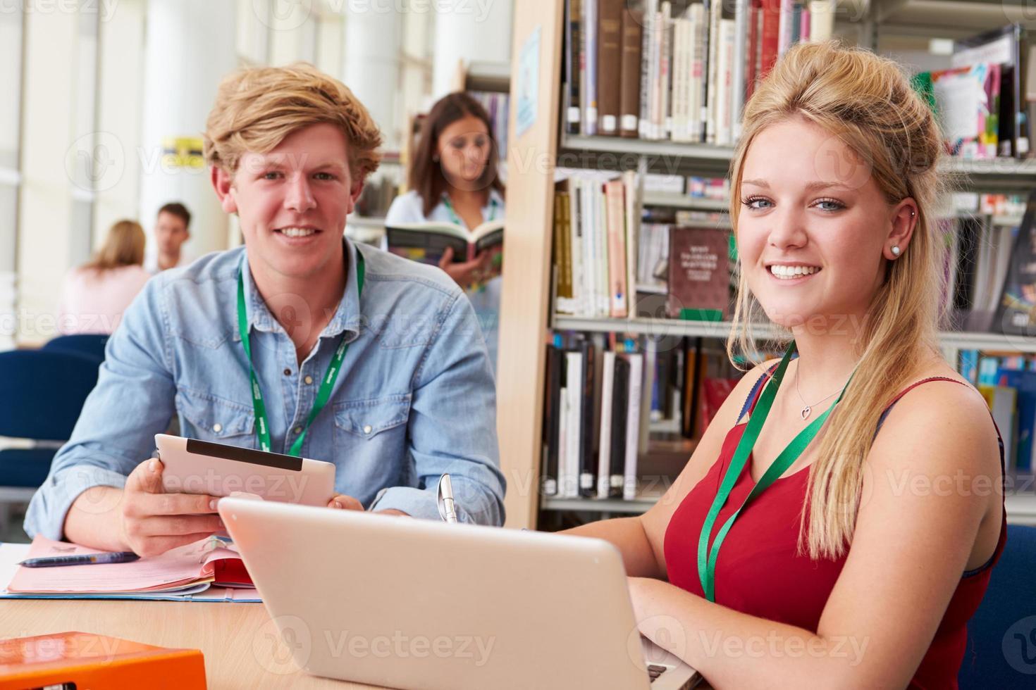 två studenter studerar tillsammans i biblioteket foto