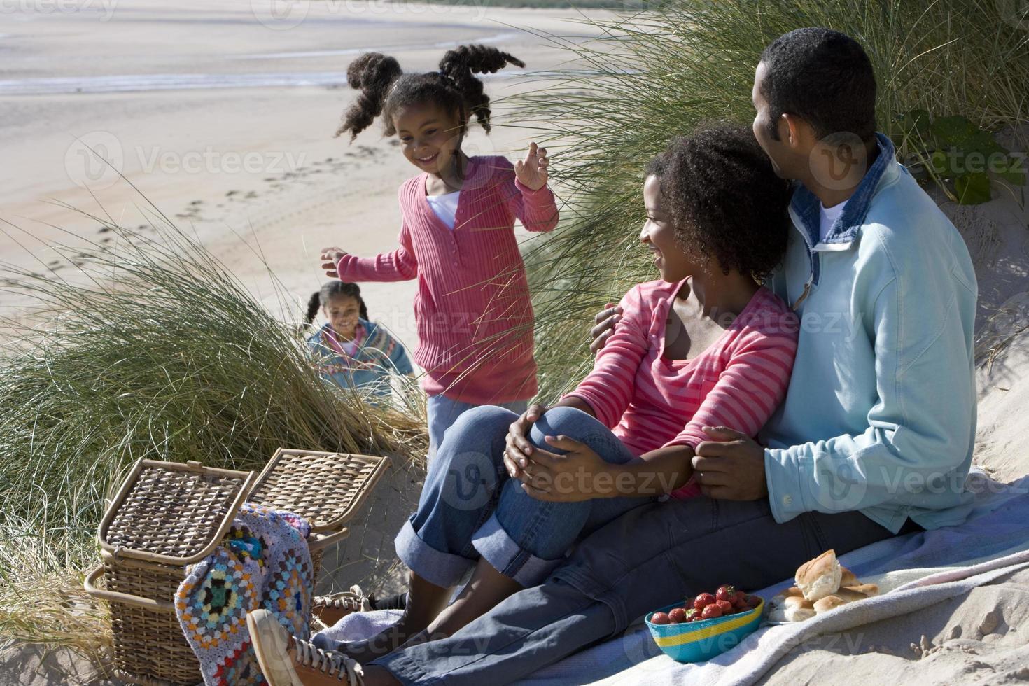 familj sitter på stranden foto