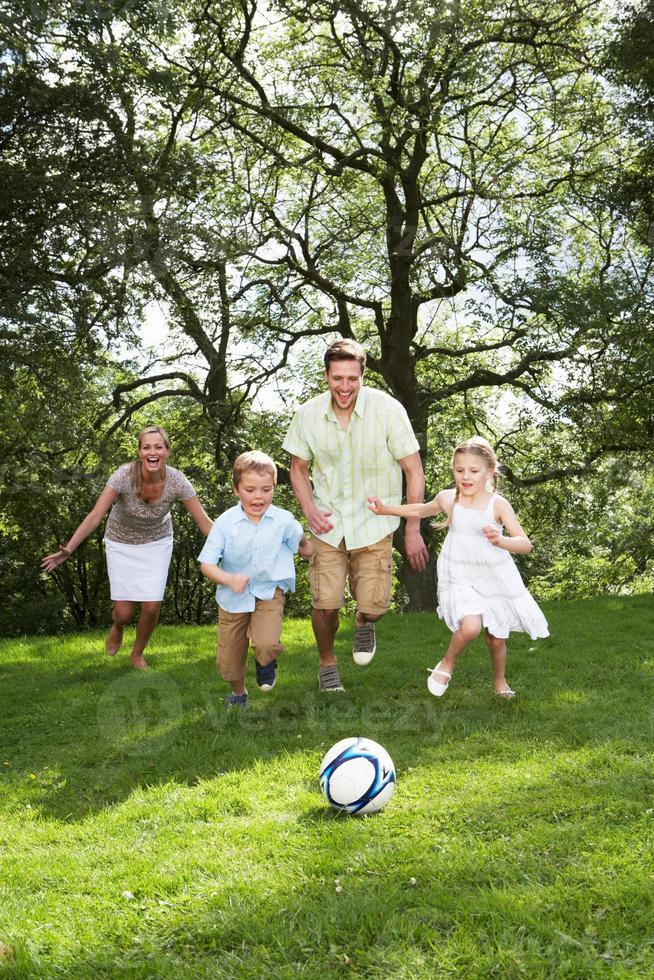 familj som spelar fotboll i trädgården foto