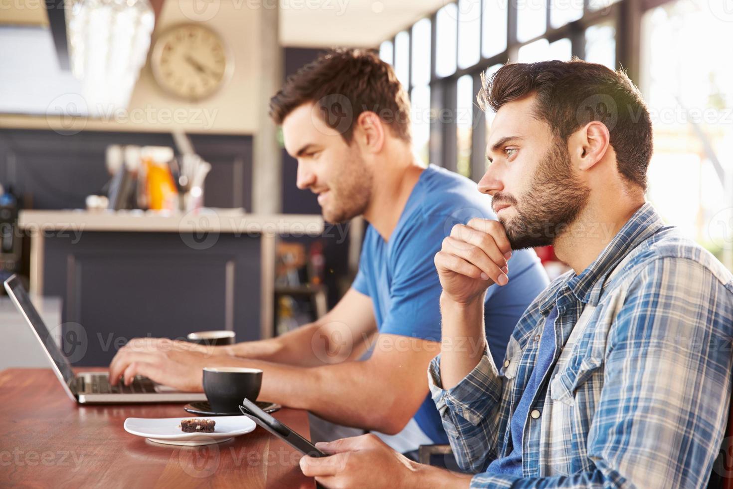 två unga män som arbetar på datorer på ett kafé foto