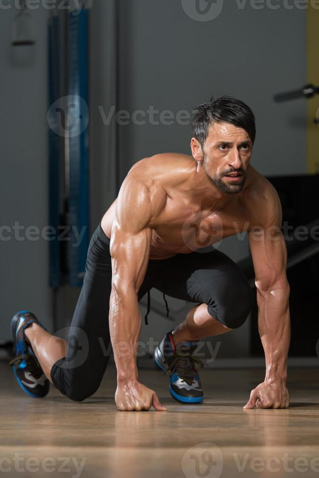 starka muskulösa män som knä på golvet foto