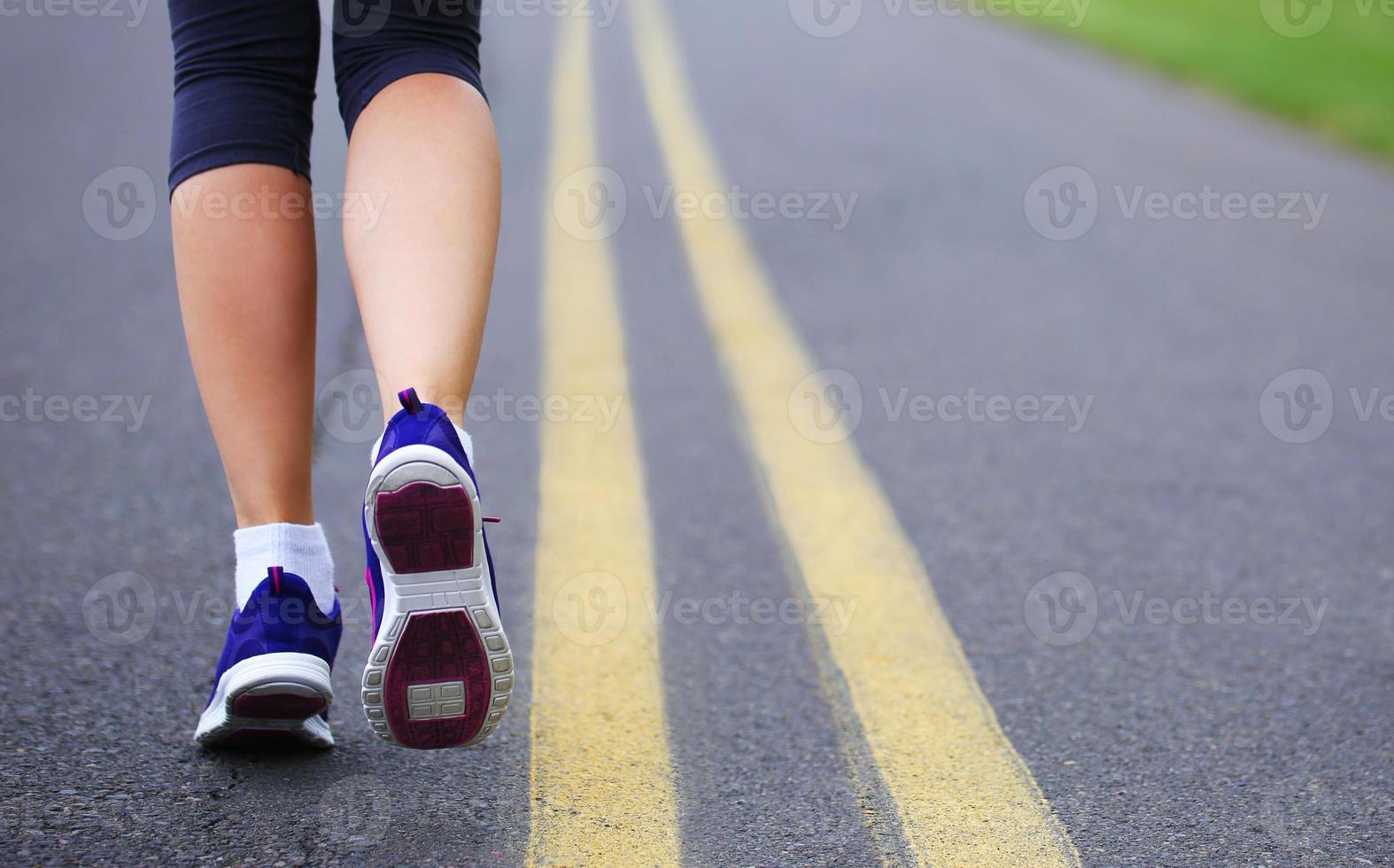 löpare kvinnliga fötter springer på vägen foto