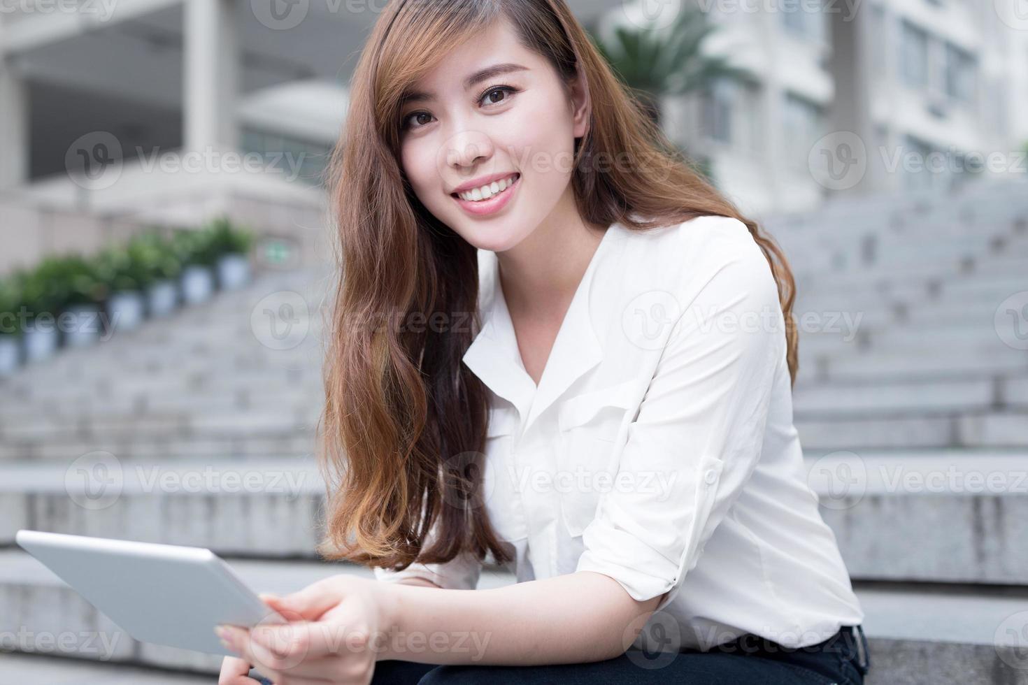asiatisk kvinnlig student som använder surfplattan på campus foto