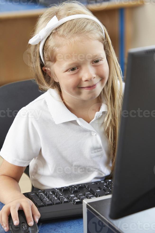 kvinnlig grundskoleelev i datorklass foto