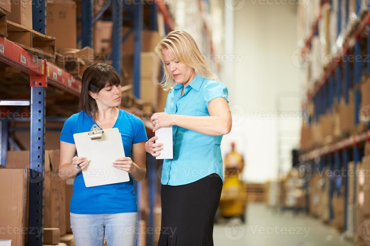 affärskvinna och kvinnlig arbetare i lager foto