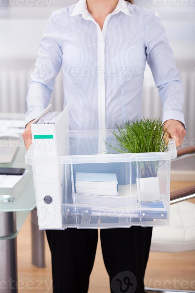 affärsman som bär kontorsmaterial foto