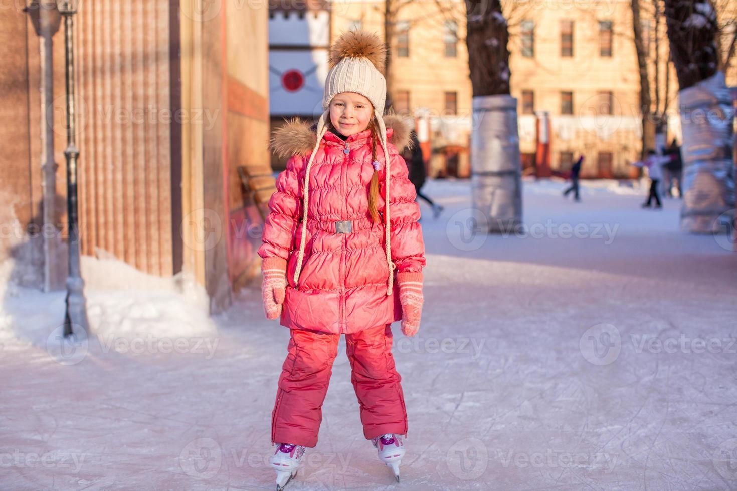 bedårande liten flicka åka skridskor på isbanan foto