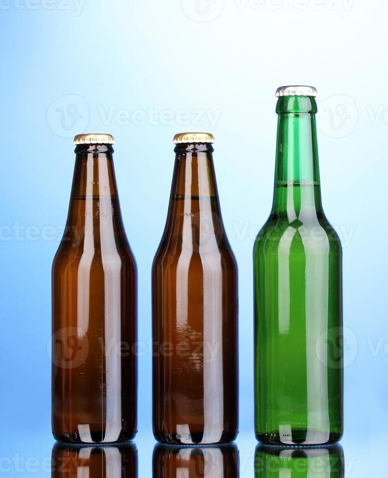 flaskor öl på blå bakgrund foto