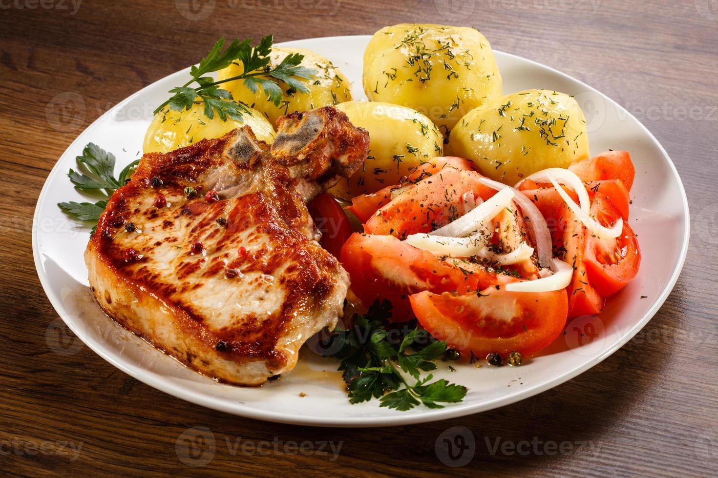 fläskkotlett, kokt potatis och grönsaker foto