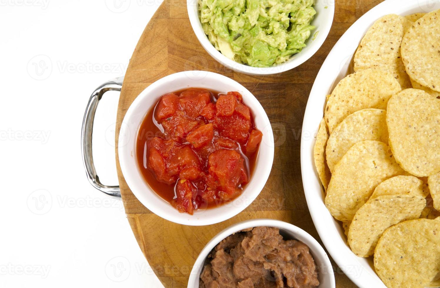 mat aptitretare chips salsa refried bönor guacamole trä skärbräda foto