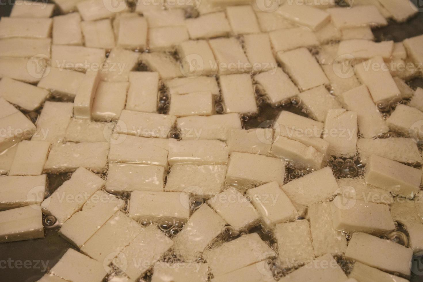 närbild på fasta tofu-kvadrater som steker i olja foto