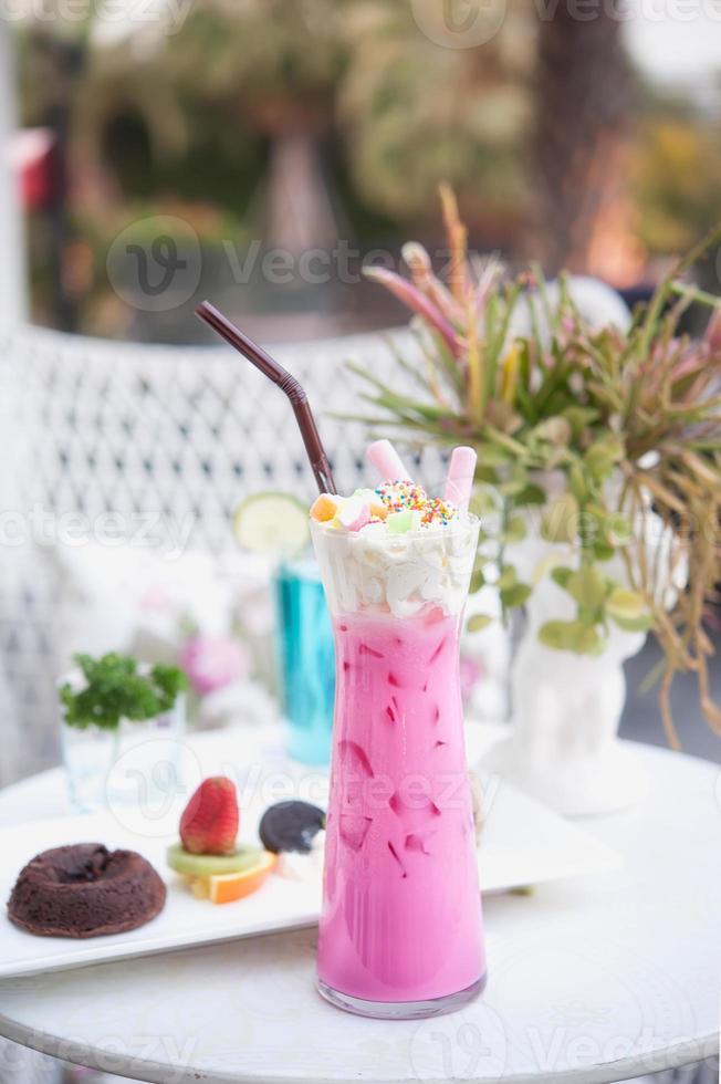 iced pink mjölk med vispad grädde på bordet foto