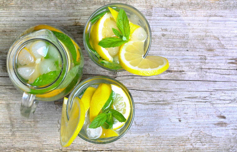 citronsaft. vatten med citron och mynta i ett glas foto