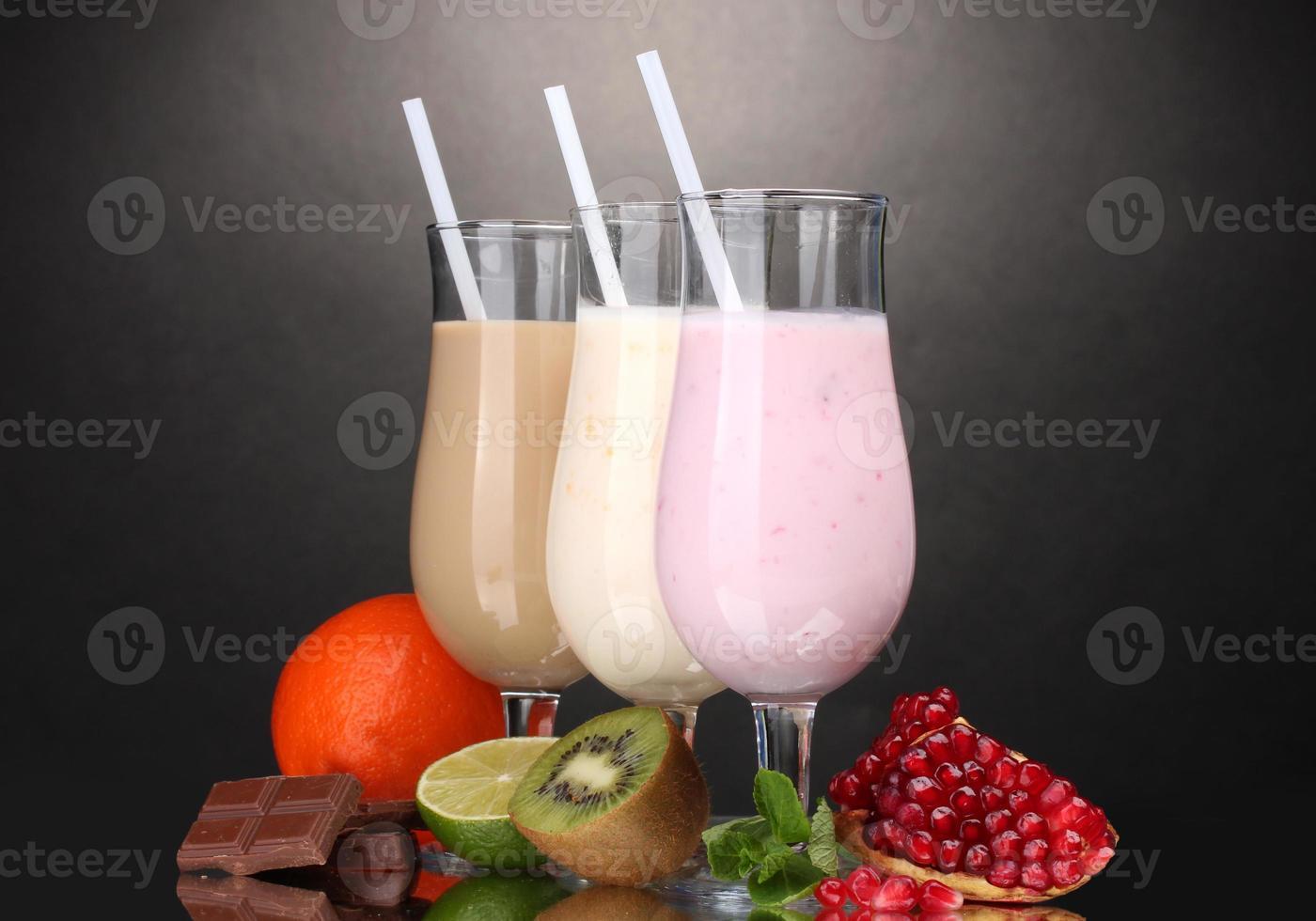 mjölk skakar med frukt och choklad på grå bakgrund foto